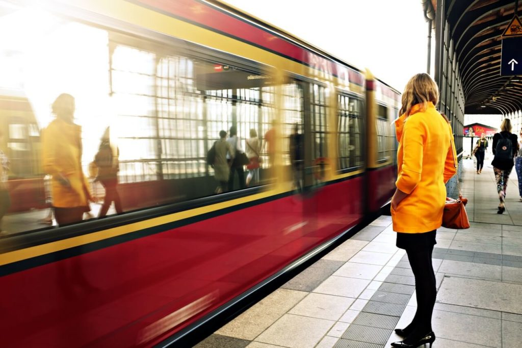 A woman in a yellow jacket standing on a train platform.
